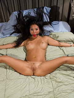 Beautiful asian captive is tied spread eage on a bed and dominated by horny lady in black rubber suit