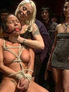Roped latina is entertaining the crowd by being tortured with clothes pegs and fucked by many guys simultaneously