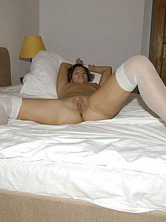 Lucky is lying nude on a pile of pillows, tied up, wearing white stockings and spreading her legs