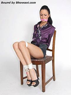 Elegant lady in purple blouse looks sexy when tied up and having scarf gag in her mouth