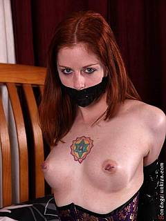 Lots of black duct tape was used for tying sexy redhead's hands behind her back