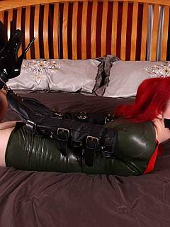 Redhead in rubber dress is restrained with kinky armbinder