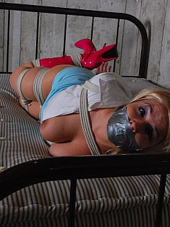 Plump captive is resting on her belly when hogtied helplessly wearing slutty pink high heel boots