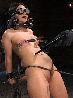 Sexy latina babe is held in place with tight leather belts and steel clamps when her body is caned and teased with vibrating sex toys