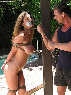 Cruel man is dragging bound MILF with a rope leash going to neck-tie her to a post in the backyard