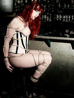 Redhead is all naked expect wearing tight corset when getting rope-tied and gagged at the bar