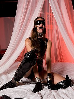 Self-bondage session where skinny model is using a set of steel cuffs and collars to turn herself helpless