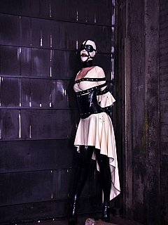 Sexy woman is experiencing rubber clothing, head mask and tight belt bondage which results elegant photo-session