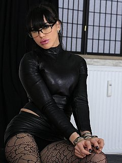 Hot secretary is dressed up in black fishnets and leather mini-dress in the scene where she is getting locked in steel shackles
