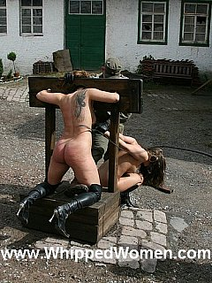 Soldiers are enjoying hot girls locked into medieval stocks for bizarre interrogation