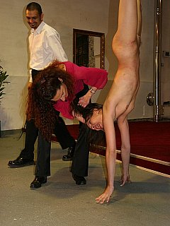 Cruel master is hair-pulling the nude girl that is suspended upside-down and using her hand to cover up pussy whip hardcore whippings