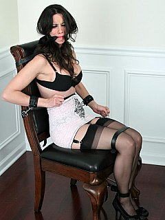 A few belts and leather handcuffs are keeping pretty babe in vintage lingerie helplessly bound to chair