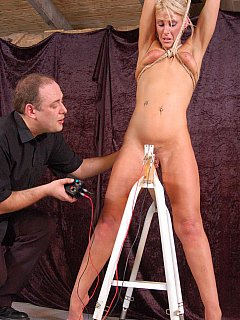 Tied up MILF is standing naked over the electrified wires having her pussy shocked every time she moves