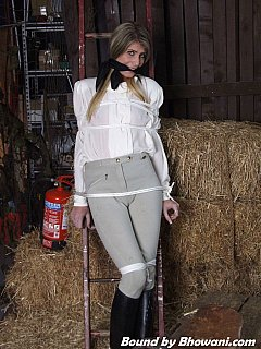 Somebody captivated hot gal in riding uniform, dragged her to the stables and tied to the wooden ladder