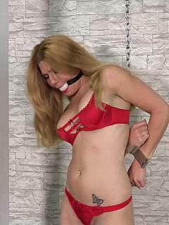 Red lingerie and high heels is the best outfit for ho woman to have her hands cuffed behind the back and gagged