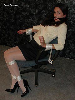 Having fun in the office: tying leggy secretary tot he chair and putting a cloth gag in her mouth