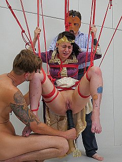 The queen of anal sex is crying in bondage suspension after a couple of dominant men fucked her in the ass with cocks and toys