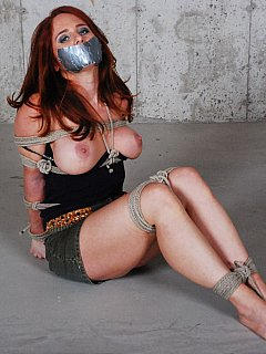 It is pleasure to see sexy redhead captive trying to escape rope bondage when rolling barefoot on the concrete