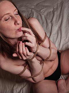 Topless girl is spending some quality time on hew own: tied up with thick rope