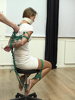 Tying up a girlfriend on a chair making sure her hands and legs are all wrapped out with ropes