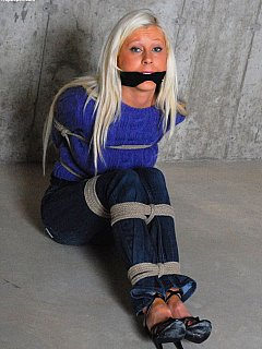 Captive gal in jeans and sweater is all rope-tied and cleave gagged