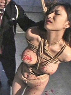 Men are having fun ripping clothing from tied up woman and tormenting her with hot wax