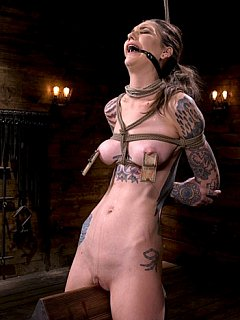 Tattooed slut is riding wooden pony when strangled with the rope noose and with mouse traps on her tits