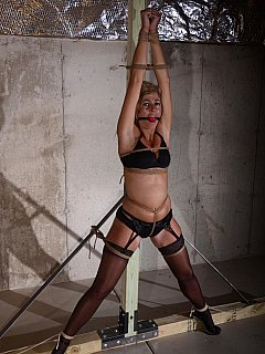 Stretching bondage looks very nice when the girl is dressed up in black lingerie and stockings