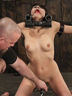 Lovely girl is nude, locked in restraints made from steel tubes and then punished